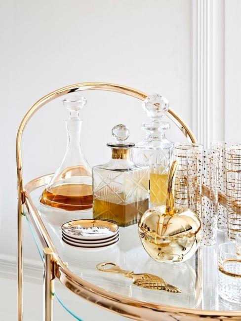 Mini bar en casa dorado con botellas de whisky y vasos