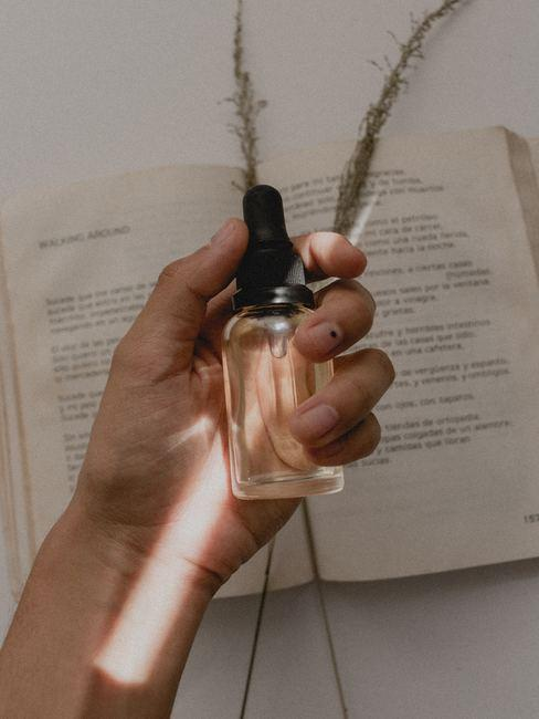 Mano de mujer sosteniendo fragancia para cosmeticos naturales
