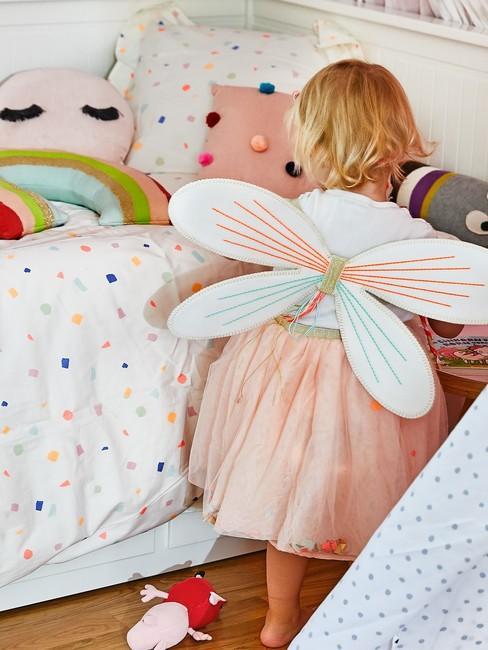Niña con alas de mariposa y ropa de cama para bebés