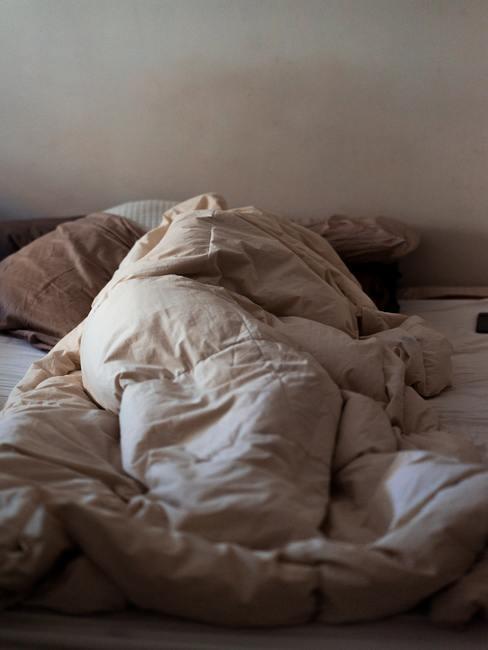 Cama deshecha y edredón amontonado sobre la cama