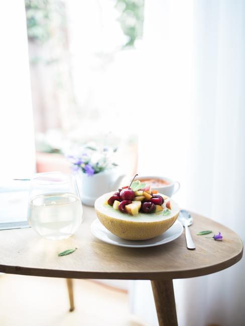 Mesa de madera con un platillo sobre el que hay medio melón con trozos de frutas dentro