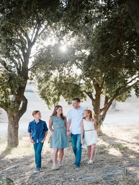 Familia posando delante de árboles con sol de fondo