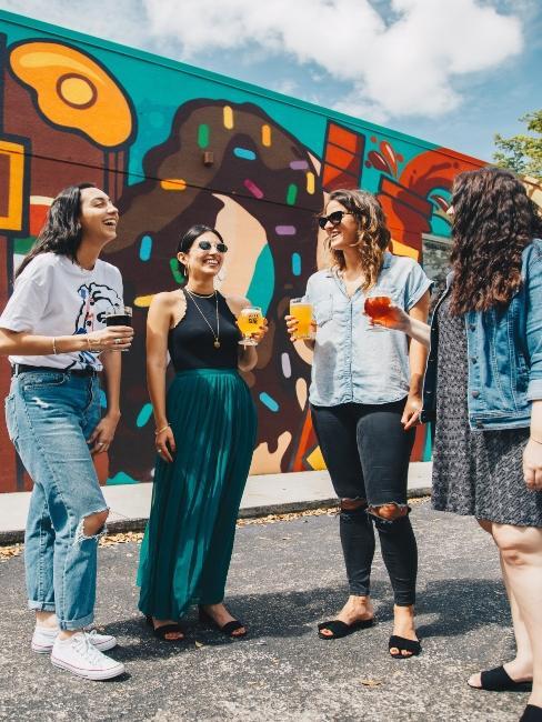 Groupe de copines prennent apéro devant mur coloré