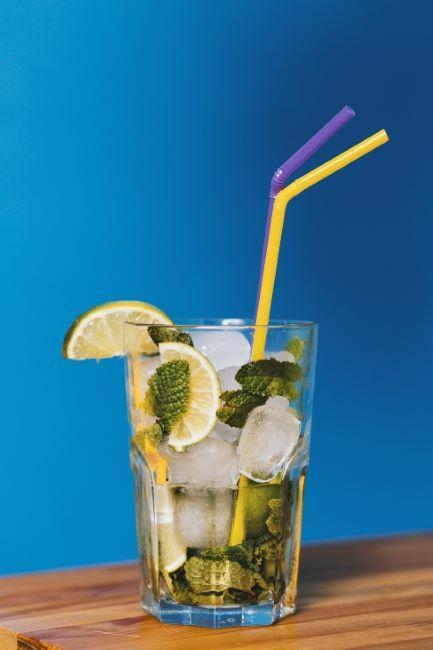 cocktail avec citron et glaçon, avec deux pailles colorées sur fond bleu