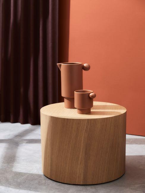 Table basse en bois avec vases couleur terracotta et rideaux foncés