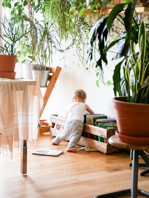 enfant qui cherche des jouets dans une boite en bois