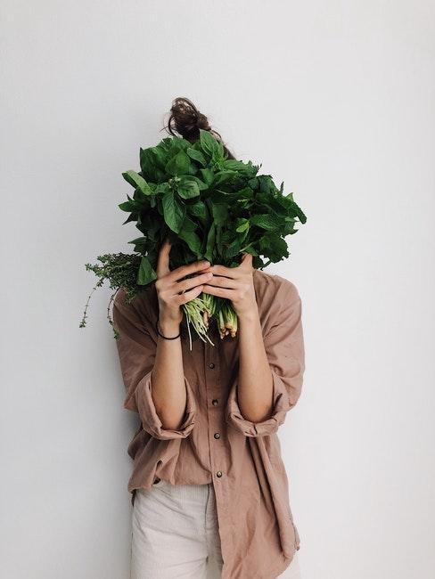 femme vêtue de beige et crème tenant des légumes devant son visages