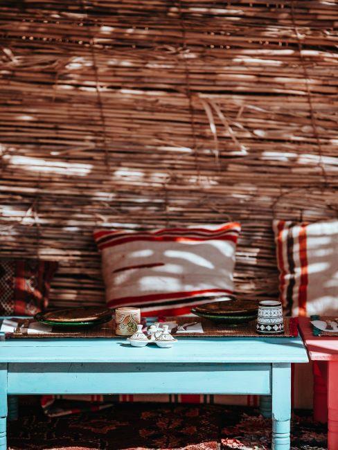 Balcon avec canisse, table basse bleue et coussins décoratifs multicolores