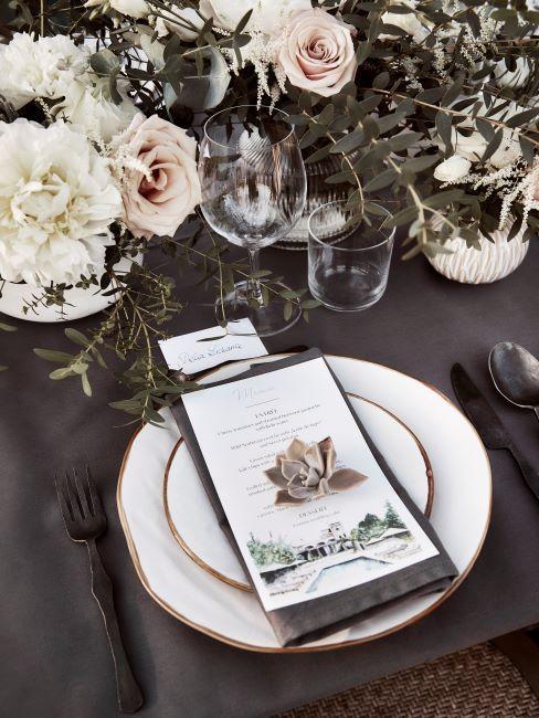 Table de mariage decoree de fleurs avec vaisselle blanche et carte de menu en carton