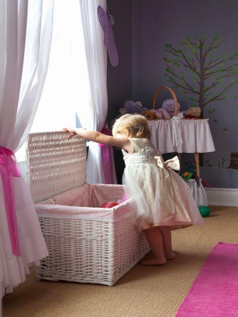 petite fille habillee en robe ouvre un grand coffre en polyrotin