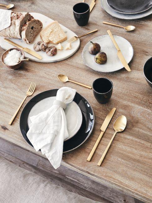 Table de petit dejeuner avec vaisselle noir, couverts dores et serviettes blanches