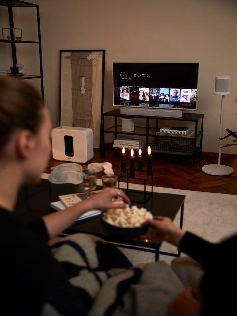 television dans salon, des personnes en train de regarder, du pop corn sur la table basse