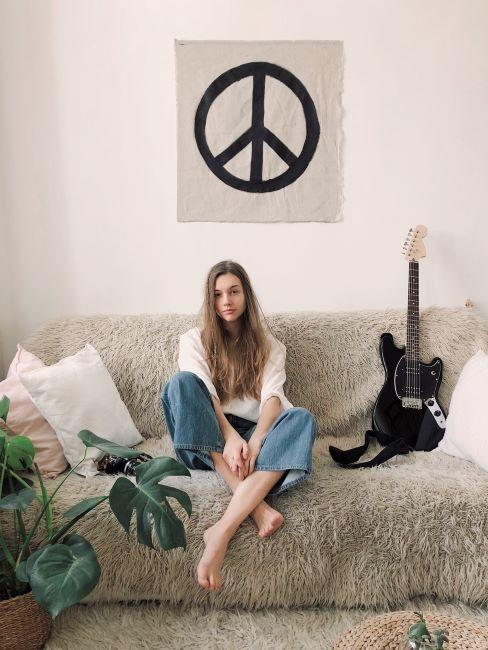 ragazza hippie seduta sul divano con simbolo della pace appeso al muro
