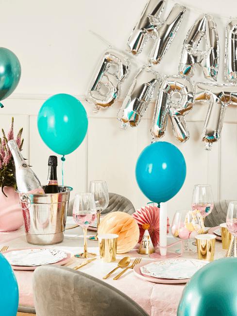 Decorazioni di compleanno con tavola, palloncini e secchiello per spumante