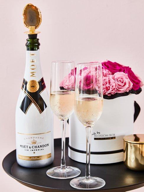 Moet champagne fles met glazen op zwarte ronde tafel met doos met roze rozen