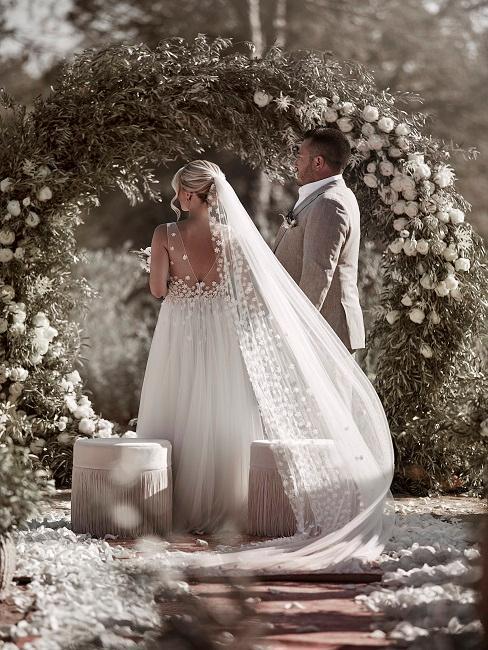 Bruidspaar buiten trouwlocatie met twee roze poefs