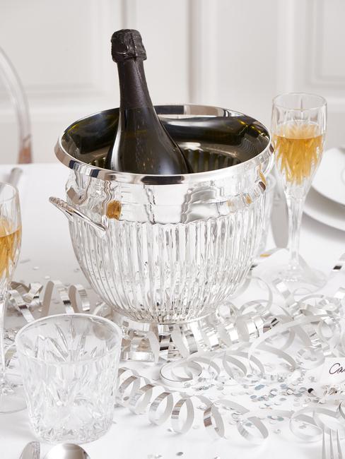 Zilveren ijsemmer met champagne en glazen