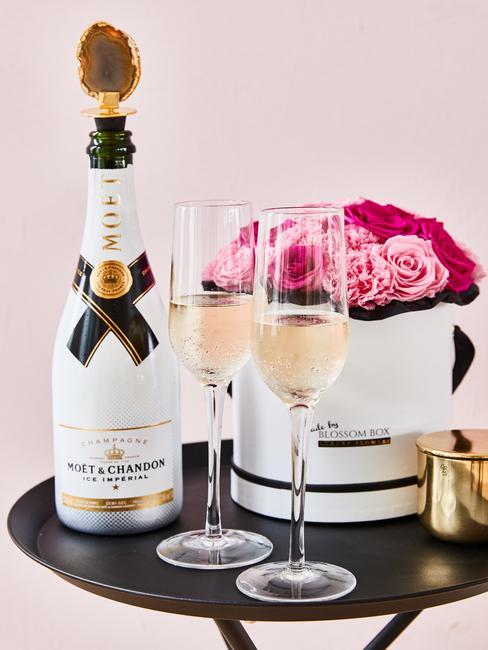 Champagnefles met twee glazen en met boeket rozen in een doos voor getuigen vragen