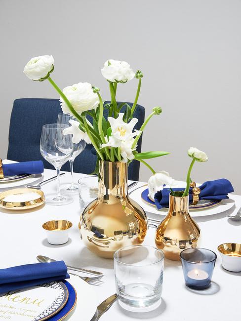 Serviesset op gedekte tafel met boeket bloemen