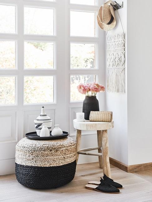 Poef en kruk met decoratieve elementen en macramé wandkleed aan de muur