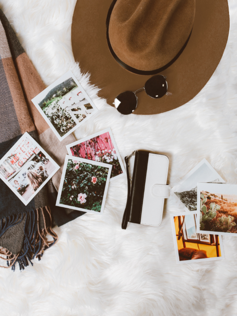 Foto's, zonnebril en hoed op bed