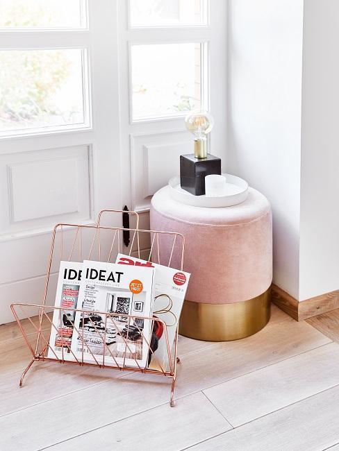 Roze pouf met tijdschriften en lamp voor witte ramen