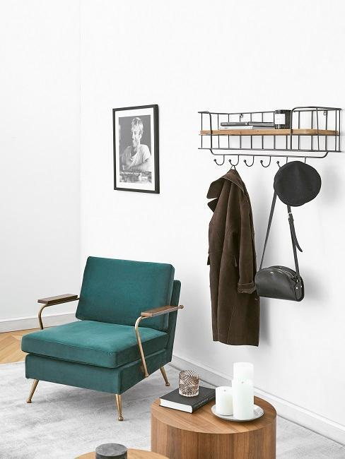 Groene stoel en houten bijsettafel naast garderobe