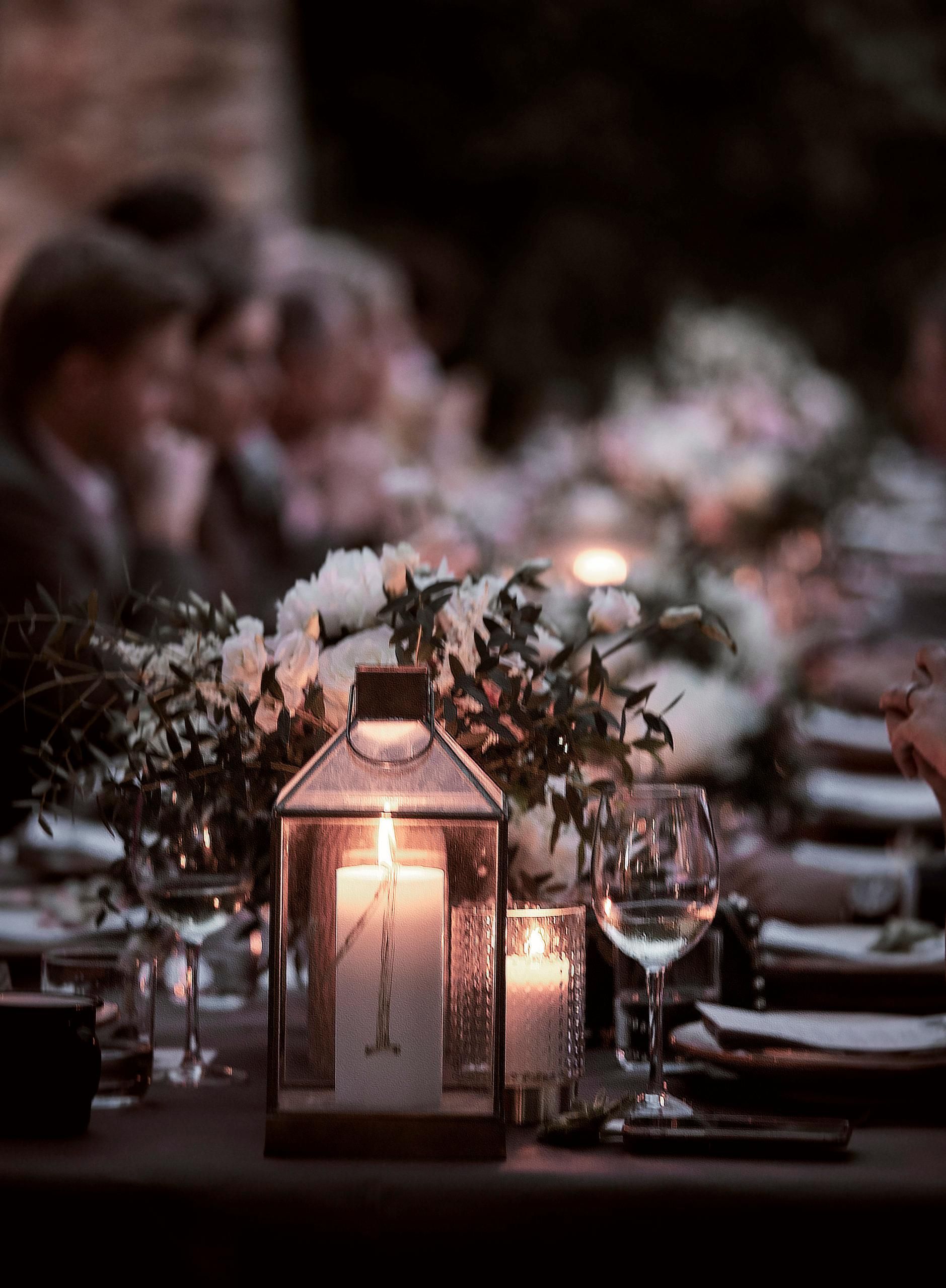 Gedekte tafel met gasten in schemerlicht met windlichten en kaarsen in boho stijl koperen huwelijk