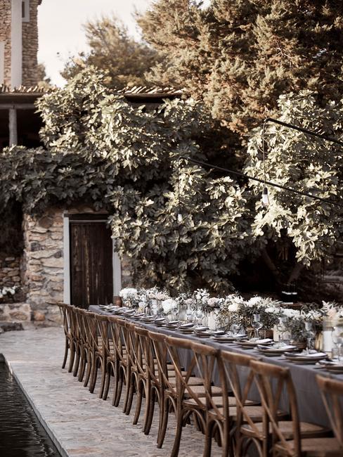 Gedekte tafel met houten stoelen buiten met boom en