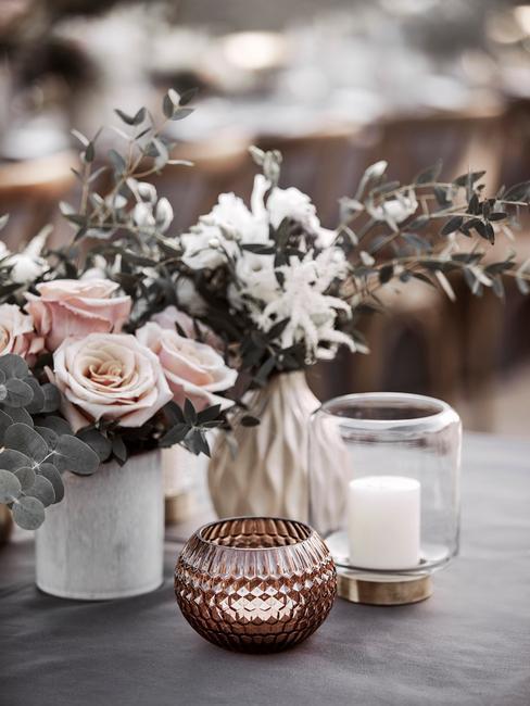 Boeket bloemen op tafel met windlichten en glazen