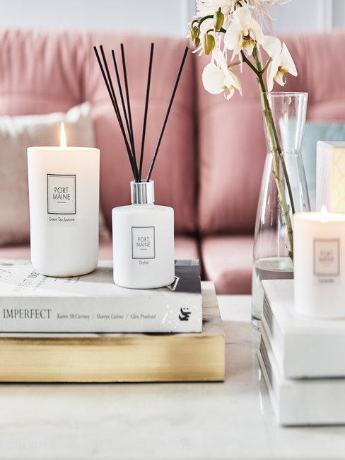 Roze bank met witte marmer bijzettafel, boeken en geurkaarsen