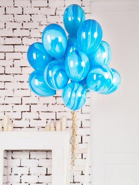 Witte baksteen muur met blauwe helium ballonnen