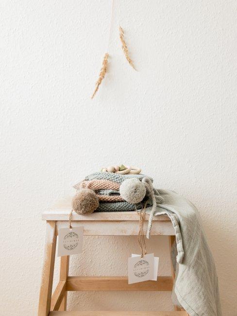 Witte muur met houten krukje met wollen muts en sjaal