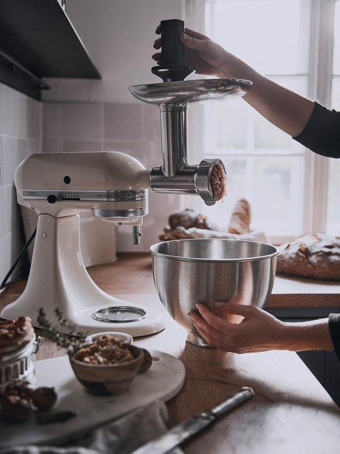Witte KitchenAid keukenmachine met hand op houten keukenblad