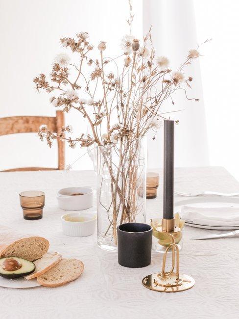 Lichte tafelsetting met gedroogde bloemen in glazen rechte vaas en grote donkere kaars in gouden kandelaar
