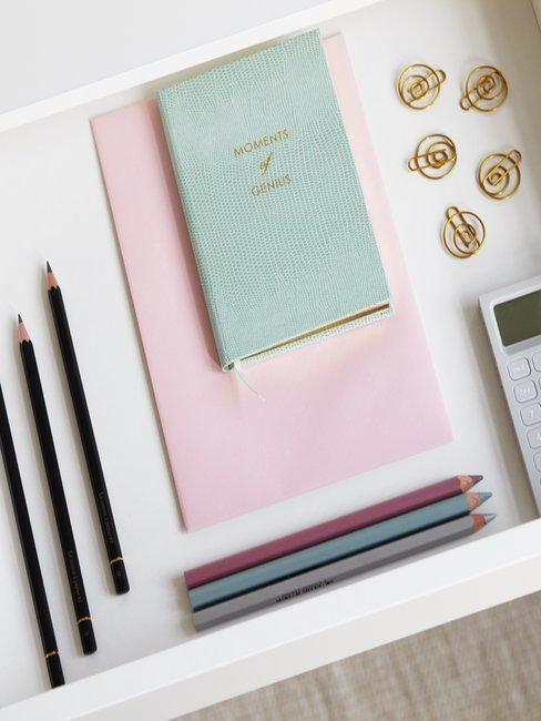 Witte laden met potloden en roze en groen notebook