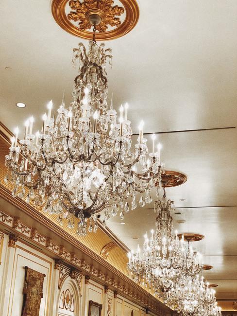 Grote glazen kroonluchters met echte kaarsen aan wit plafond