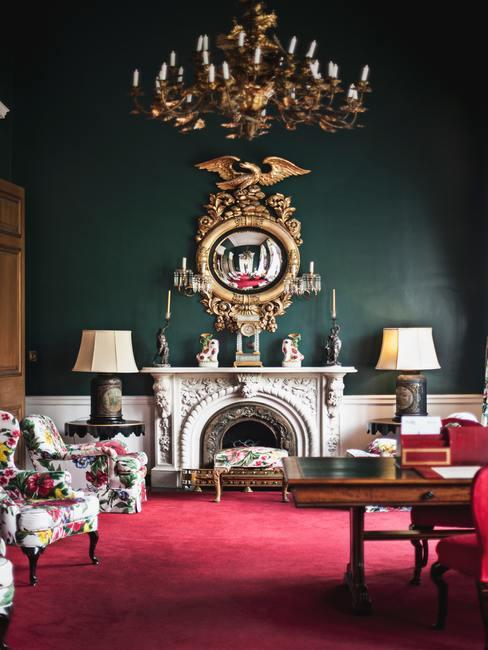 Groene wand met grote witte marmere schouw en gouden schilderij er boven kamer met rode vloerbedekking
