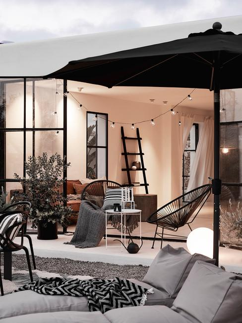 Balkon met zwarte parasol en loungeset
