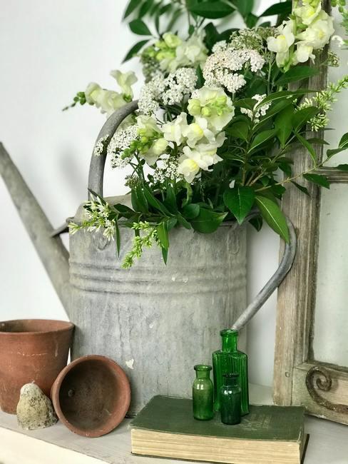 Grijze gieter op tafel met bloemen er in