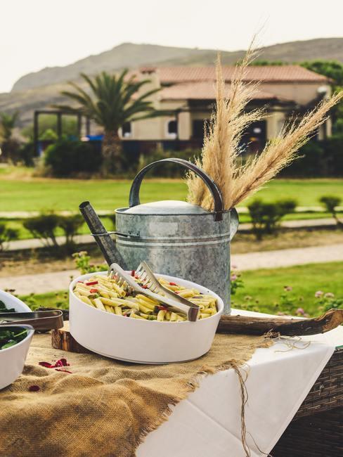 Zilveren gieter en witte schaal met groenten op houten tafel