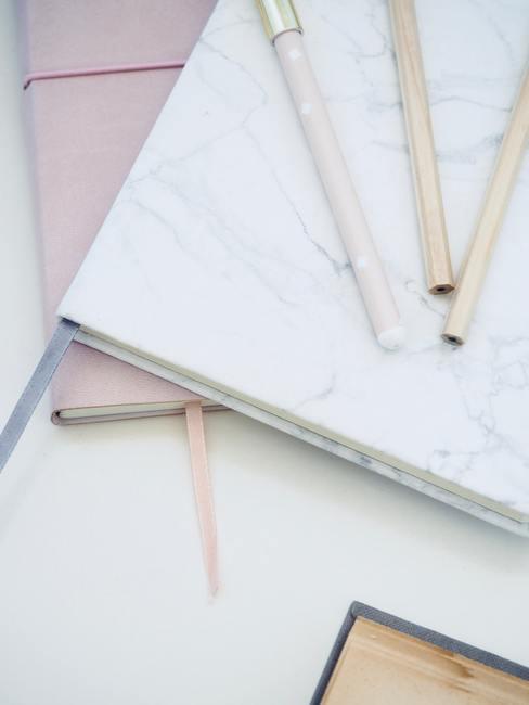 Witte achtergrond met notitieboeken en pennen