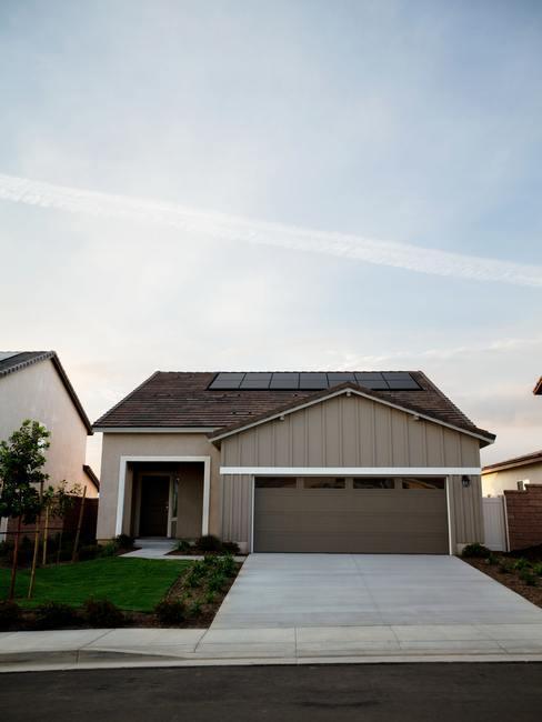 Opricht met bruin houten huis en zonnepanelen op het dak