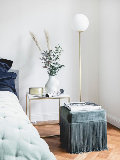 Slaapkamer met groene poef en groene sprei met nachtkastje en staanlamp met gouden details