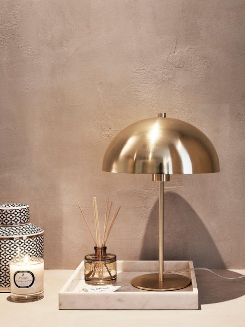 Gouden tafellamp op sitetable voor zandkleur muur
