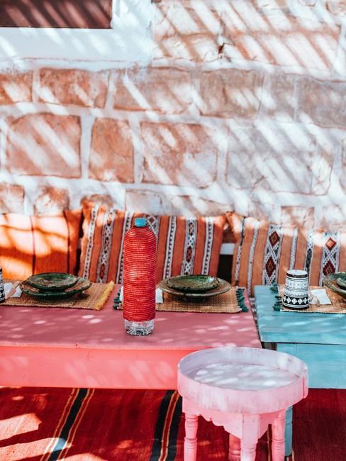 Stenenmuur met roze en blauwe tafel met gekleurde kussens