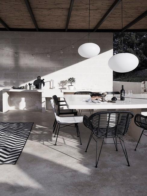 Grijze buitenkeuken met witte tafel en zwarte tuinstoelen