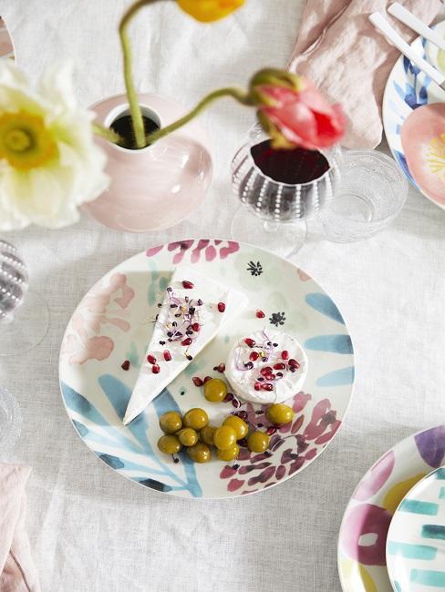Moederdag ontbijt gebak op kleurrijk bordje met bloemen in kleine vaasjes