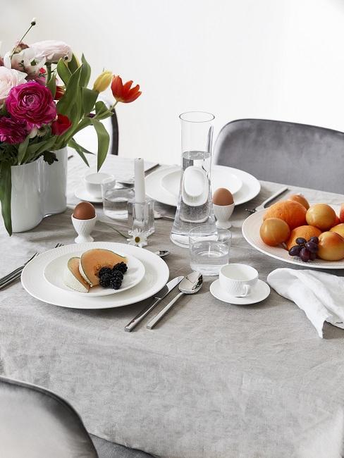 Moederdagontbijt op wit servies op grijze tafel met stoel