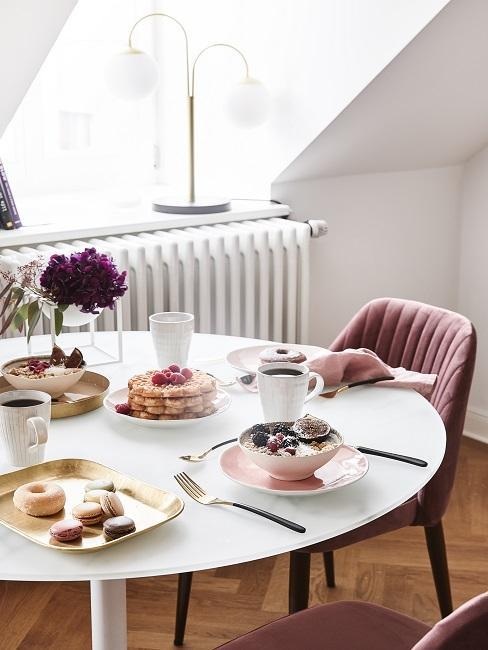 Ontbijttafel onder schuin dak met oud roze velvet stoelen